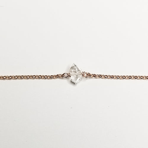 a herkimer diamond on rose gold chain with a white background