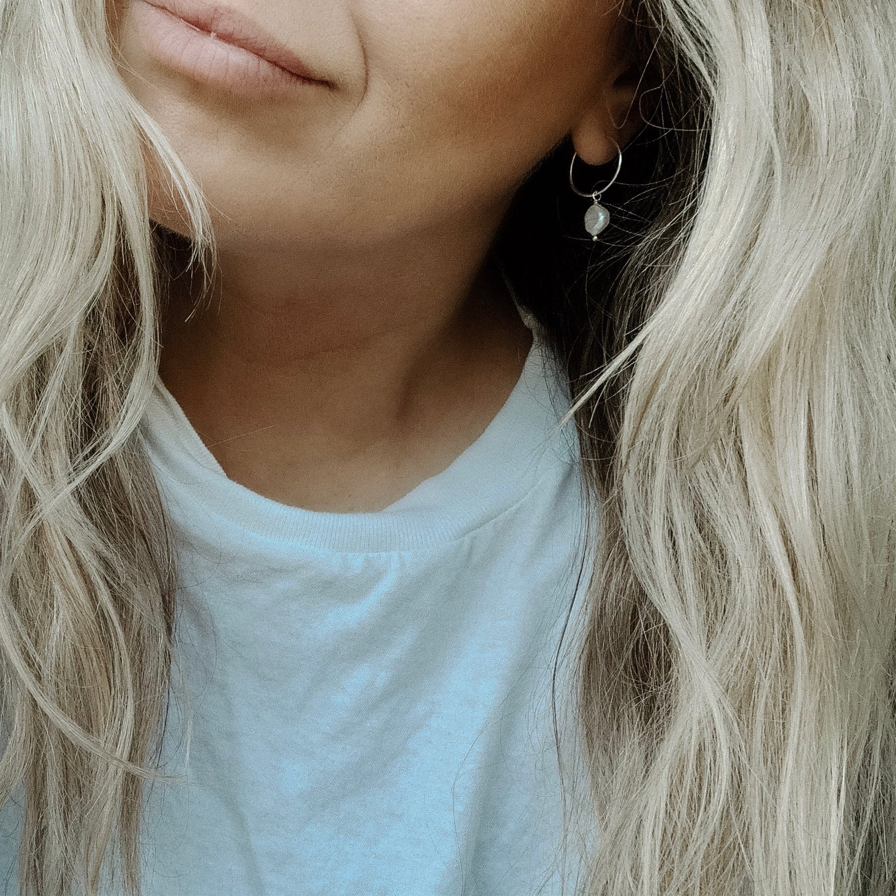 a cropped selfie of a woman wearing a white tee shirt with blonde hair, wearing small silver hoop earrings that have a single pearl