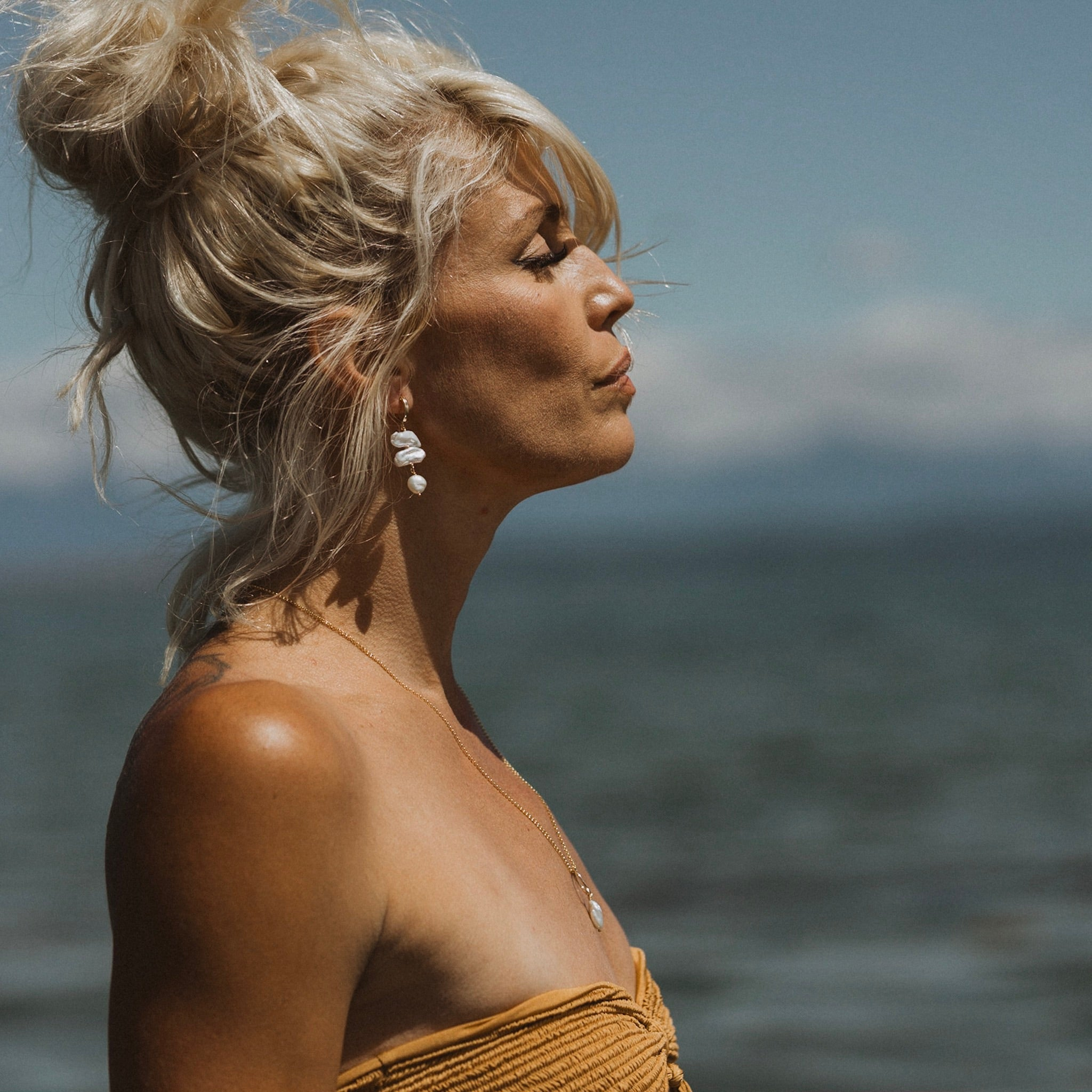a side profile of a woman with a messy bun in her hair, wearing dangly stacked pearl earrings and a long gold necklace with a pearl pendant. Show in front of a blurred ocean and sky