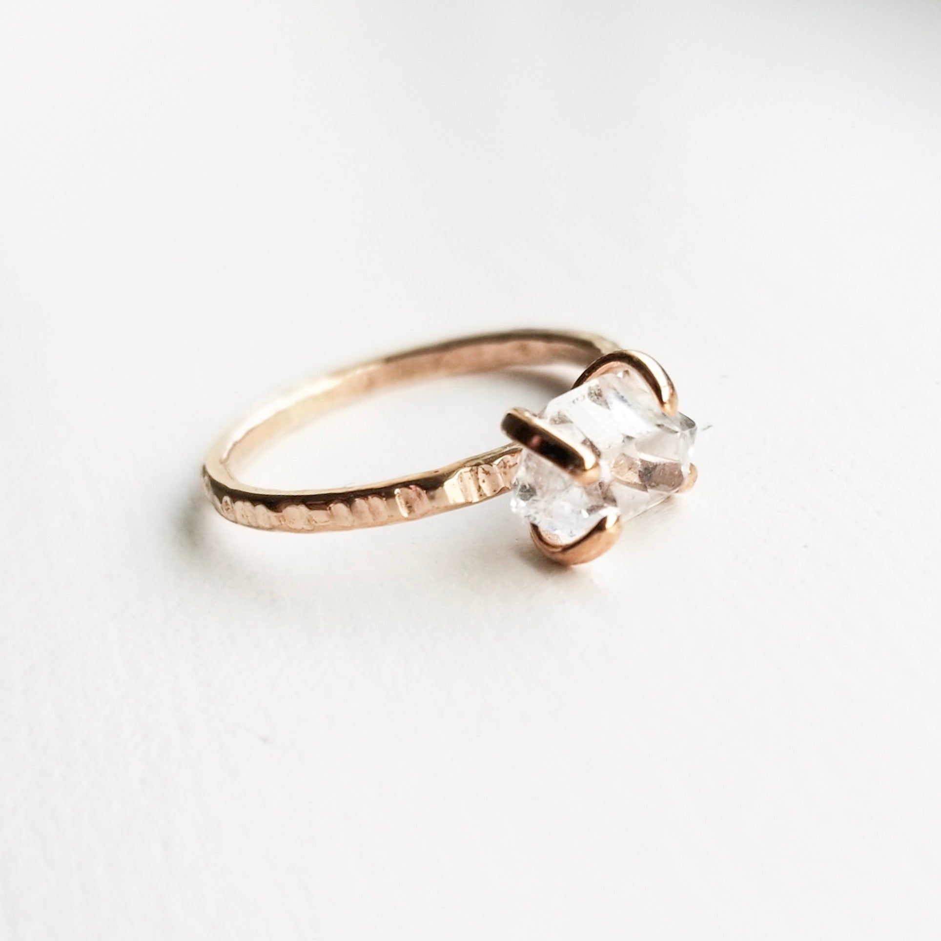 a gold claw style ring with a herkimer diamond on a white background