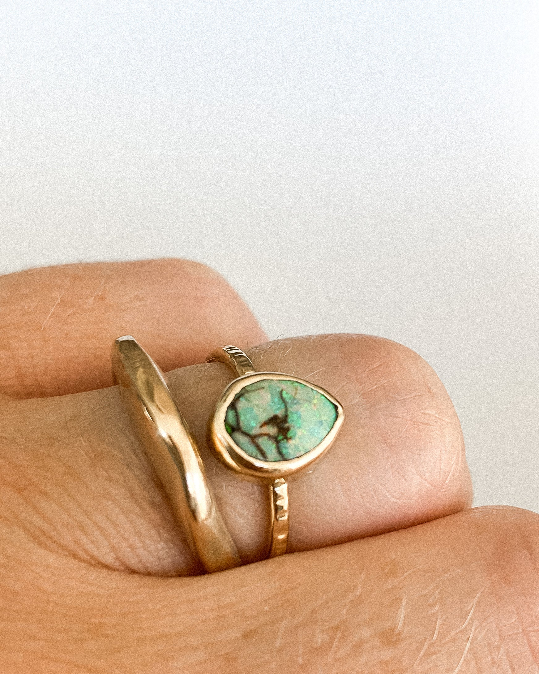 a close up of a finger wearing a gold band ring and a tear drop shaped turquoise ring wrapped in gold
