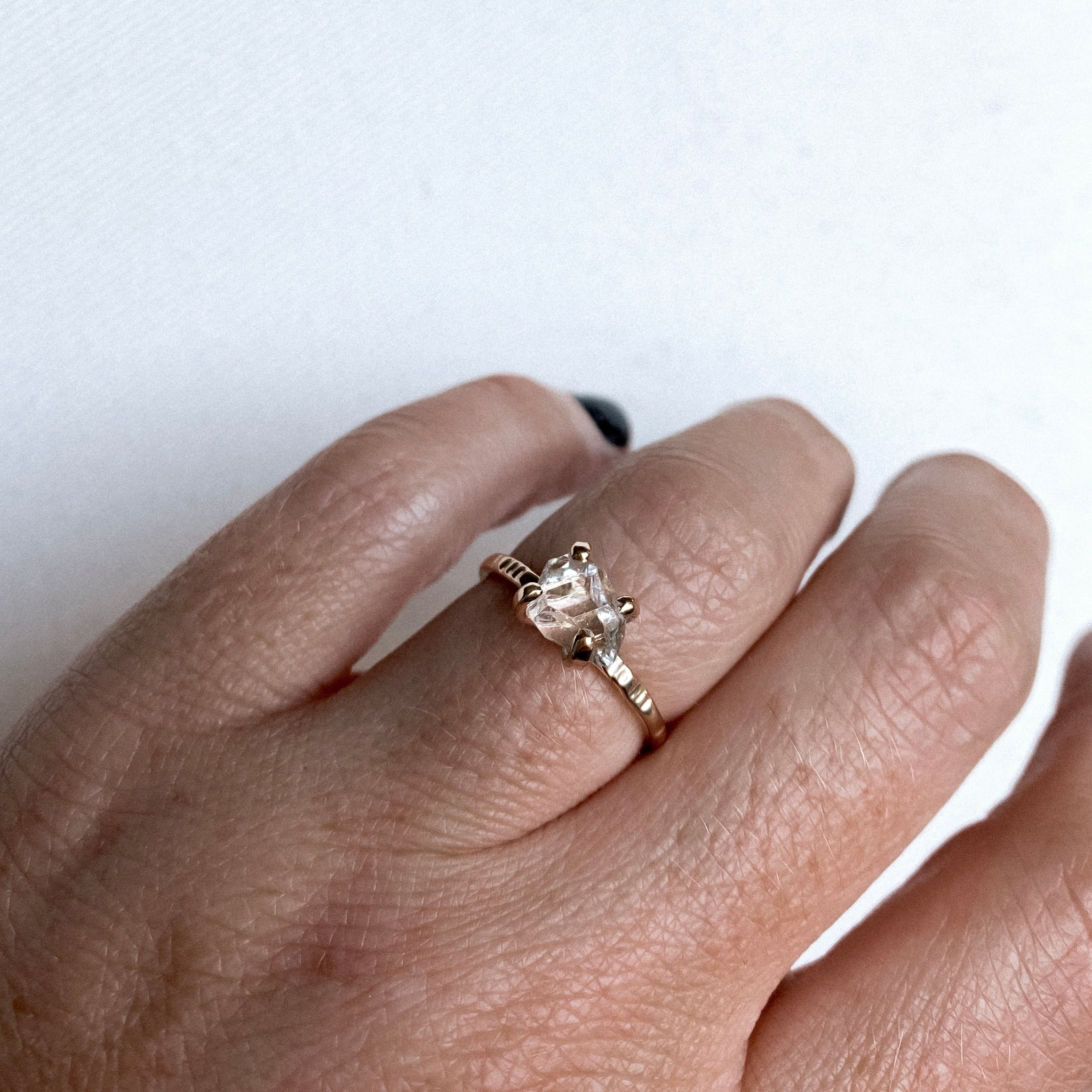 a close up of a finger wearing a gold claw style ring with a herkimer diamond