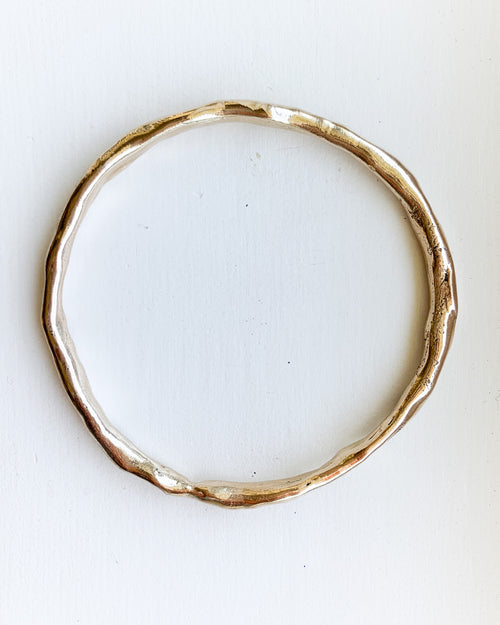 a hand formed bronze bangle bracelet shown on a white background