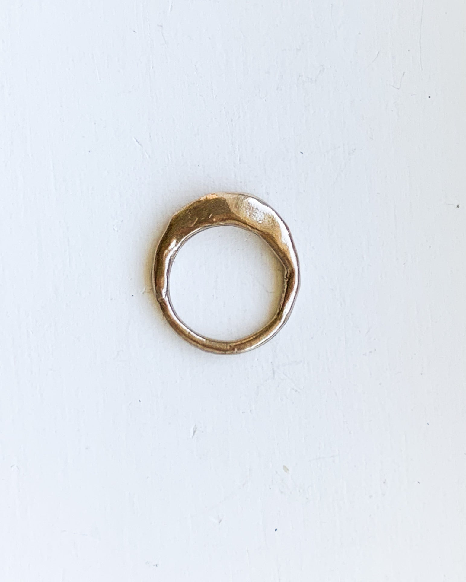 a hand formed bronze ring made from wax cast in metal on a white background