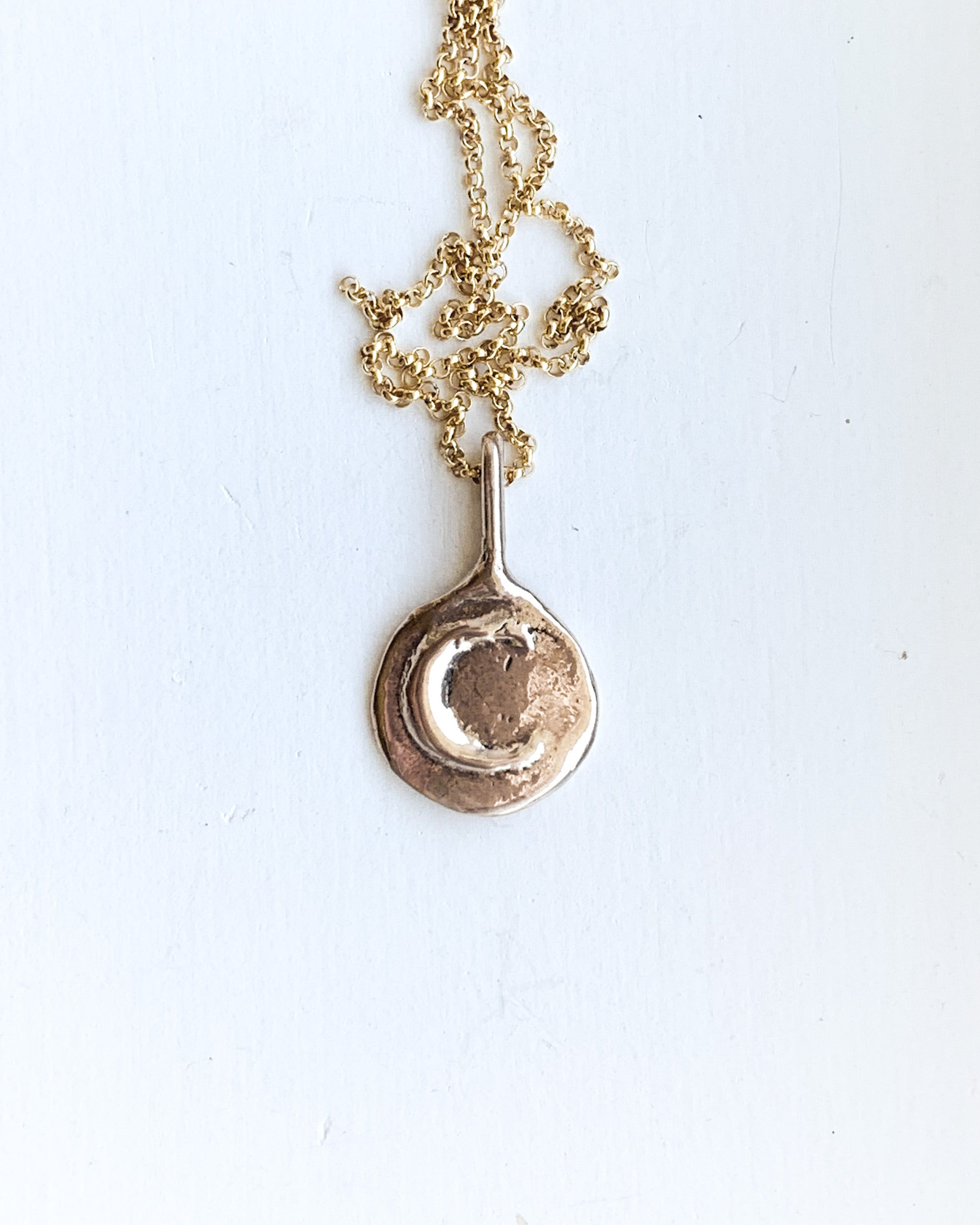 a hand formed bronze moon pendant with a gold chain on a white backgroud
