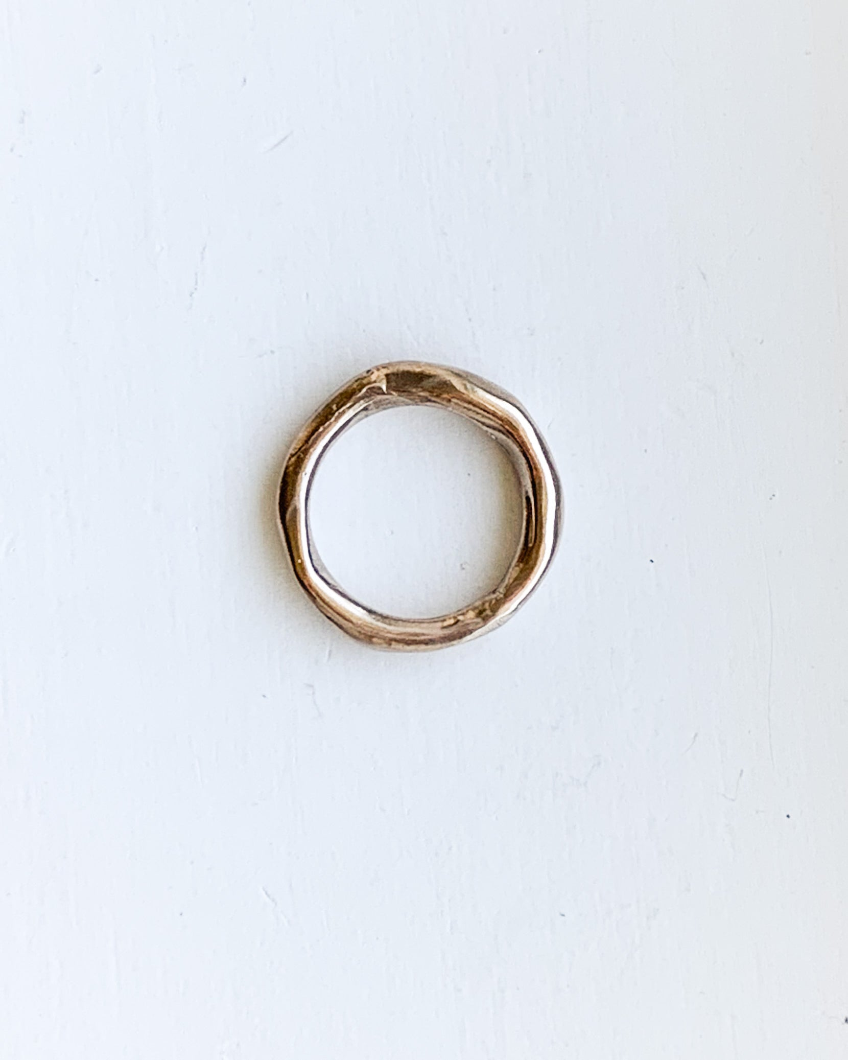 a hand formed bronze ring made from wax cast in metal shown on a white background