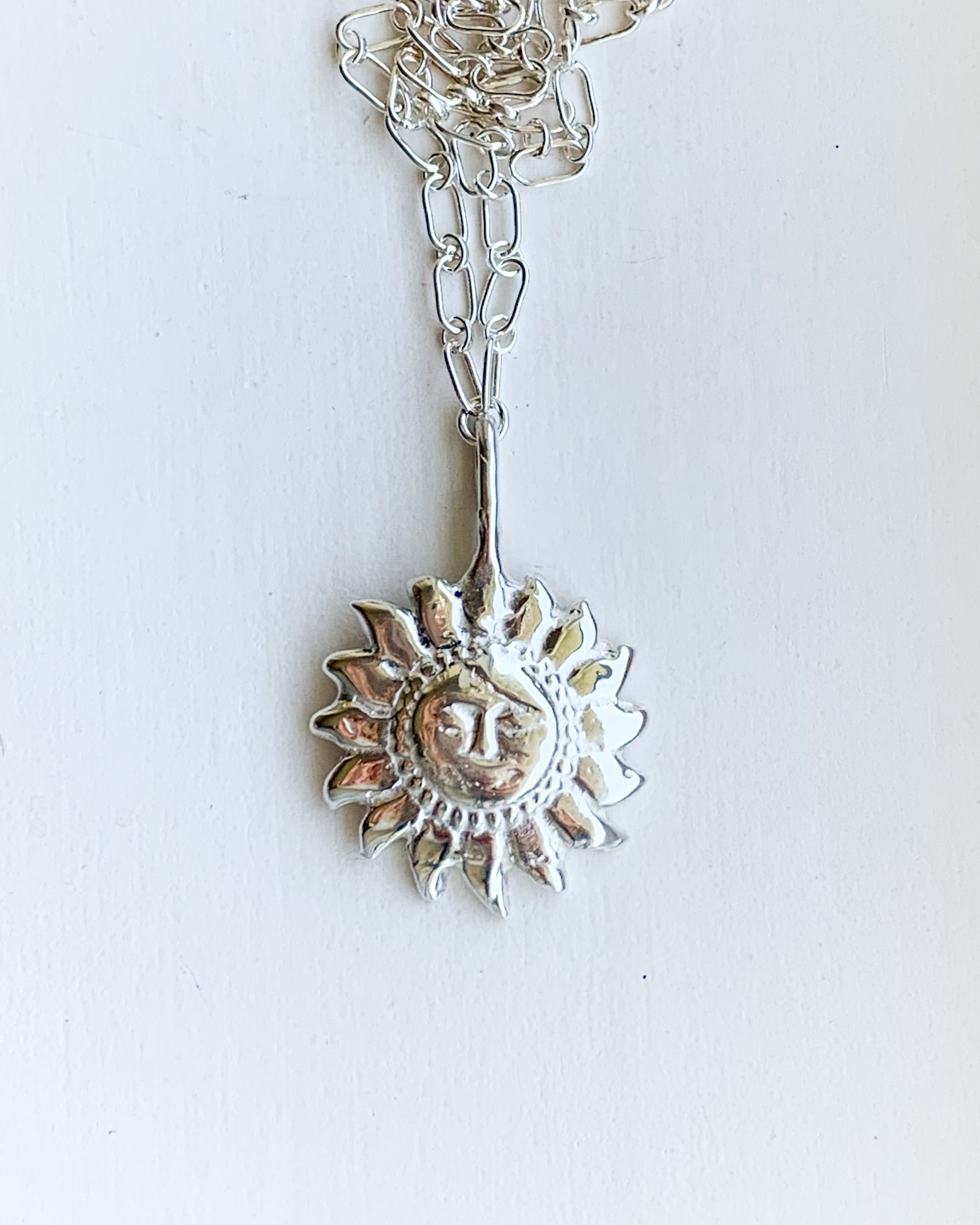 a silver sun shaped pendant necklace on a silver chain, shown on a white background