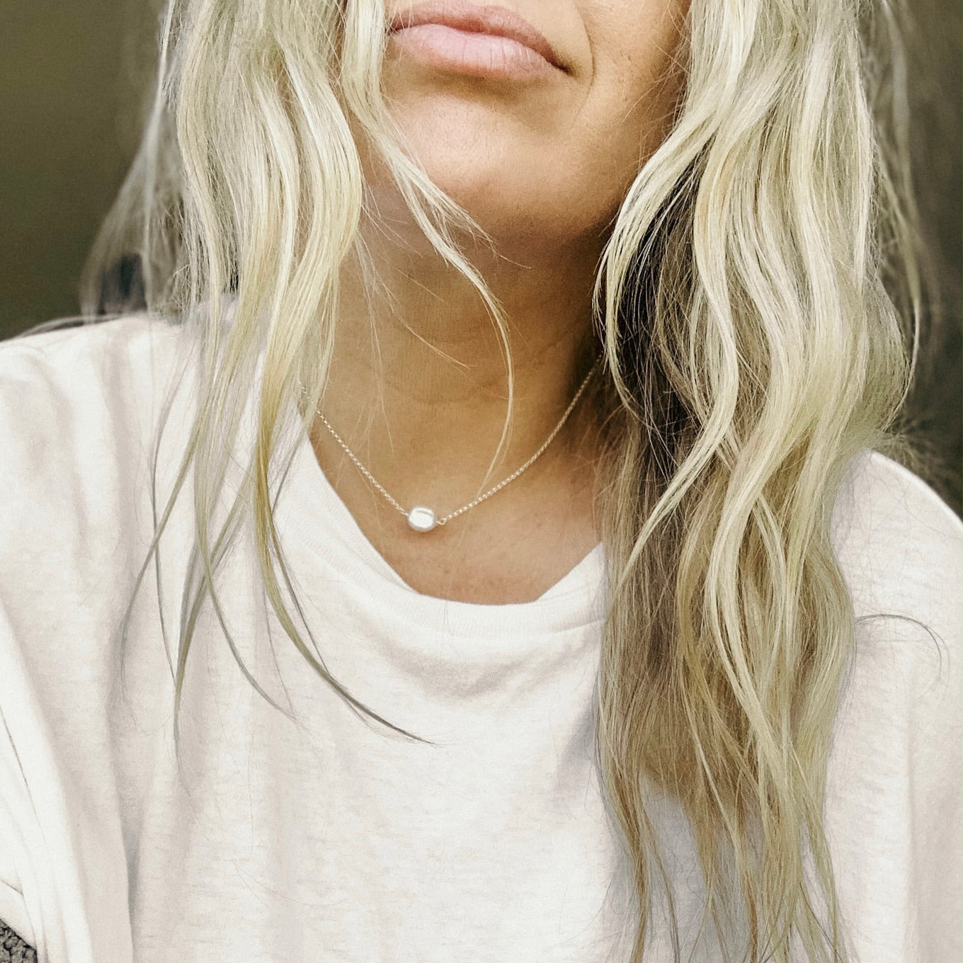 a selfie of a blonde woman wearing a white tee shirt and small pearl necklace on a silver chain