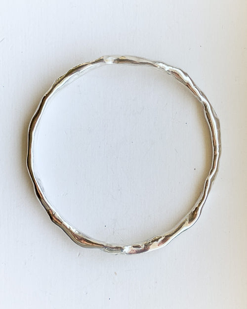 a handformed silver bangle bracelet shown on a white background