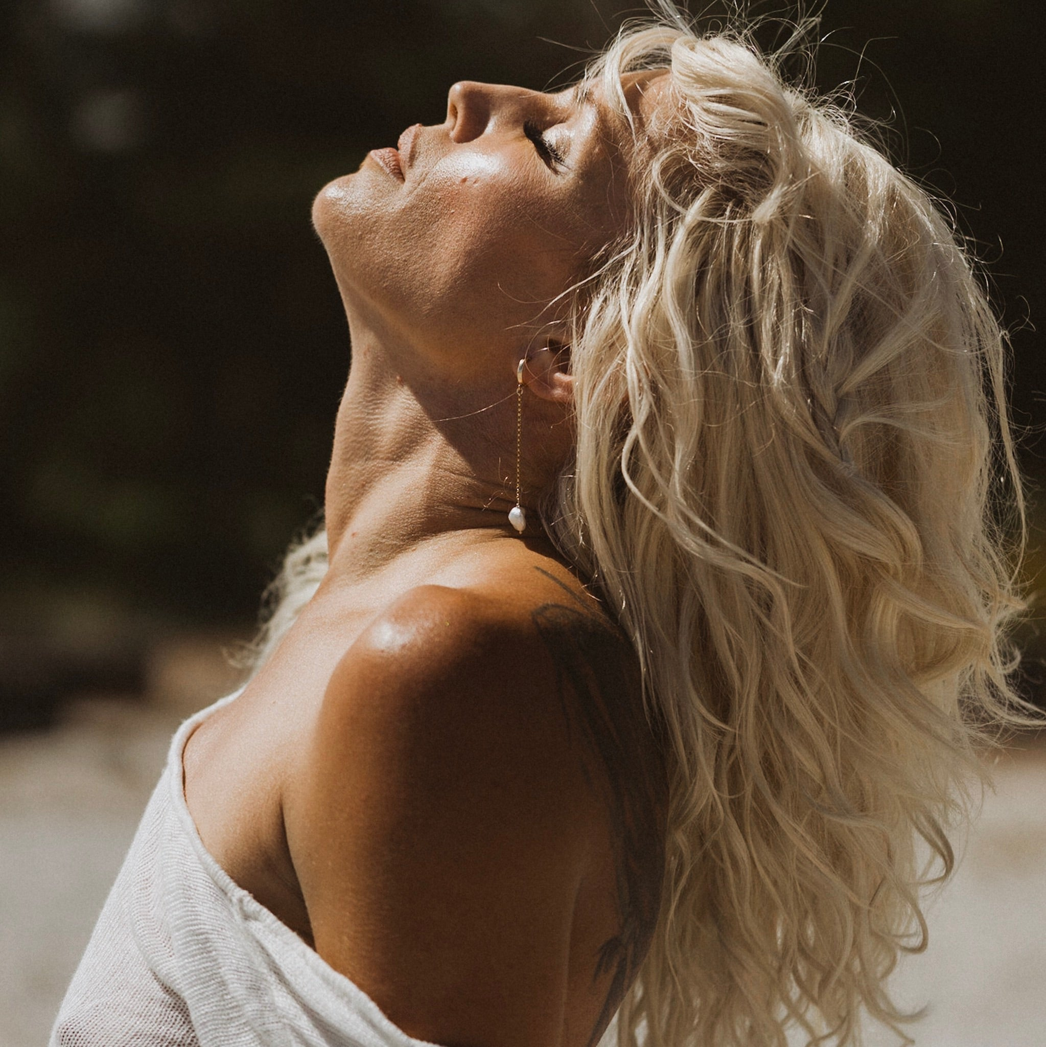 a side profile shot of a blonde woman with a large back tattoo, wearing a white top and dangly gold drop pearl naiad earrings looking to the sky with sun on her face