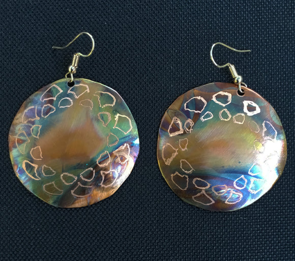 Round copper flame painted earring that measures 1 1/6th with geometric etching around the piece