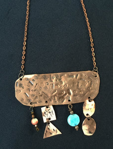 Copper rectangle that has 4 dangle beading and copper geometric patterns hanging from the piece