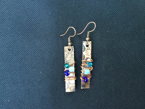 Small rectangle with beads wrapped on wire in blue going around piece
