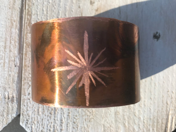 Starburst design has  been etched into flame painted 1 1/2 inch copper cuff