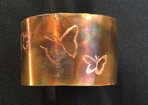 Copper flame painted cuff where 3 butterflies have been etched into the cuff