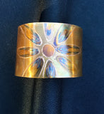Flamed into a blossom pattern on copper and then etched around the blossom pattern