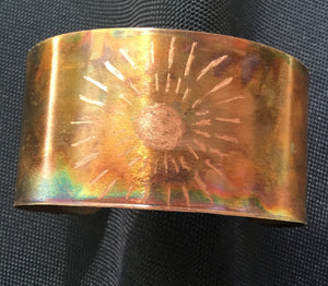 1 1/4th inch wide cuff with lines in a circle of dashes surrounding the flame painted piece