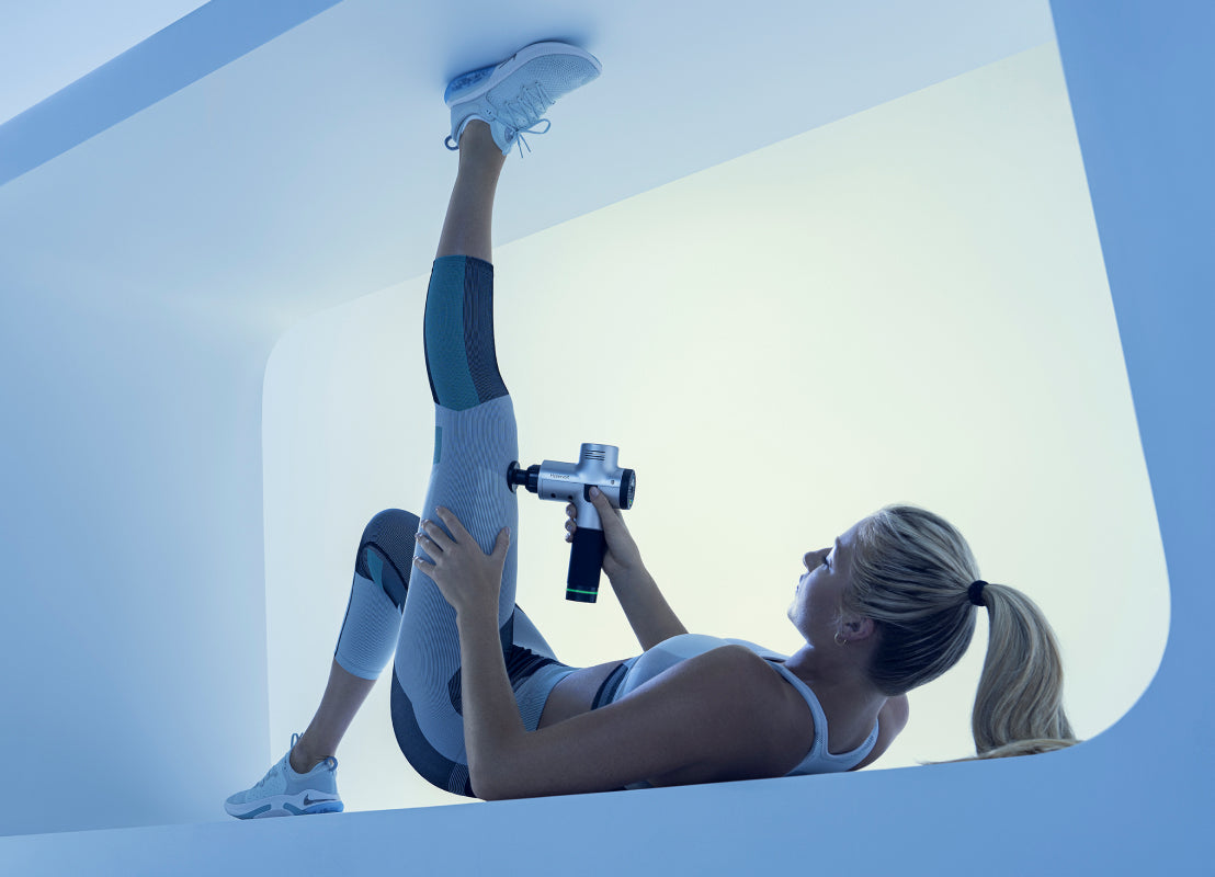 woman lying down wearing gray workout clothes using Hyperice Hypervolt on her leg