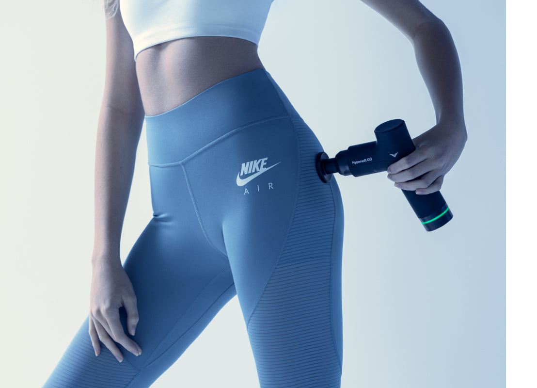 Woman in a white sports top and blue leggins using the Hypervolt GO on her left hip