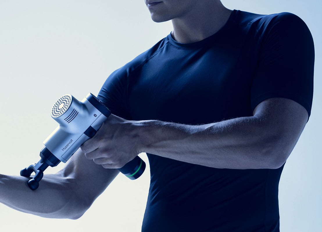 man in black athletic shirt using Hyperice Hypervolt on his right forearm