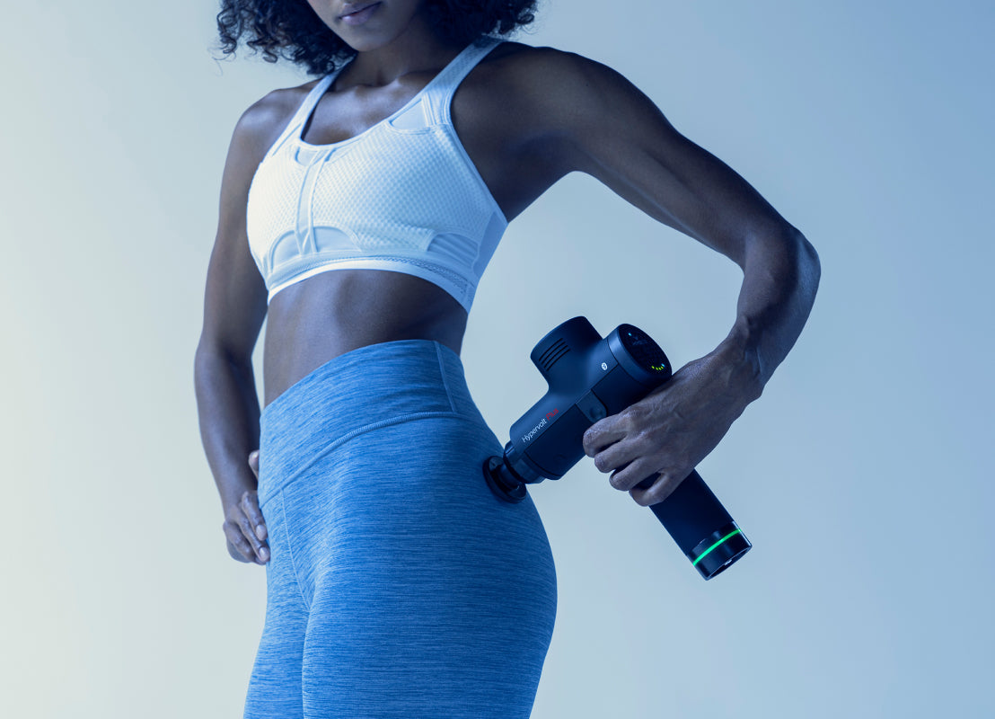 women in white sports shirt and gray workout leggings holding a black Hperive Hypervolt in her left hand on her right hip