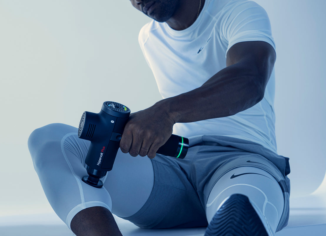 man in white athletic shirt and gray shorts using the  black Hyperice Hypervolt in his left hand on his right leg