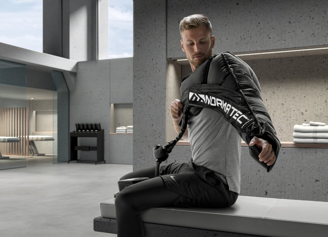a man on a gray bench wearing workout clothing wearing a Normatec on his left arm