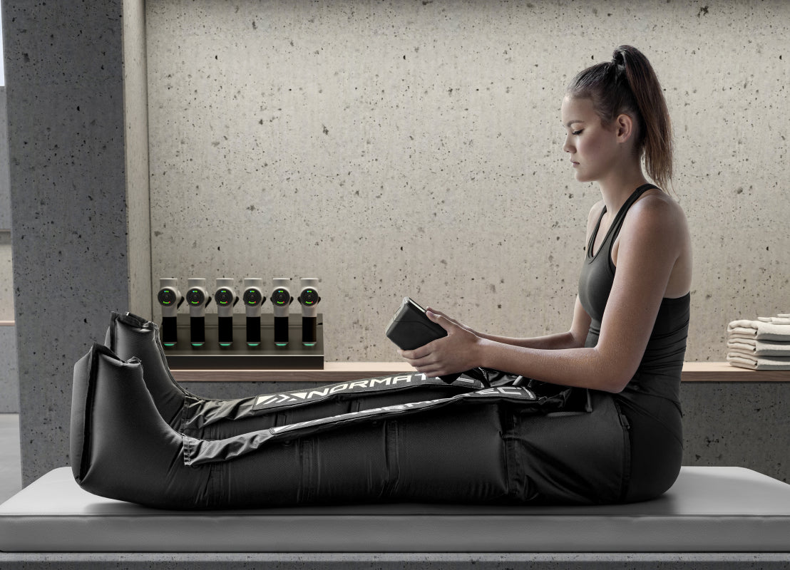 a woman sitting on a gray bench wearing a black workout tanktop while using the black Normatec on her legs