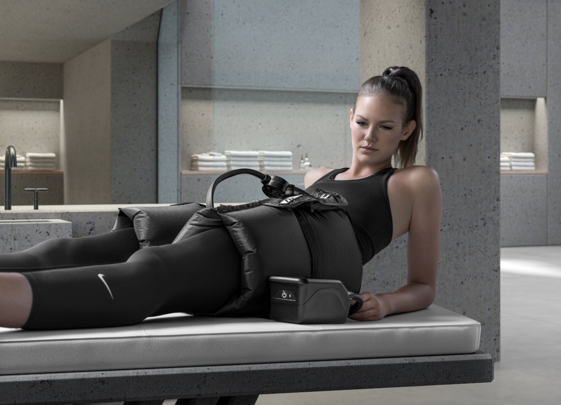 a woman laying down on a gray bench wearing black athletic clothing and using the Normatec on her hips