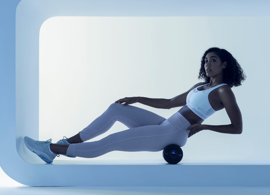 woman wearing gray and white workout clothes laying on her back using the Vyper on her hip