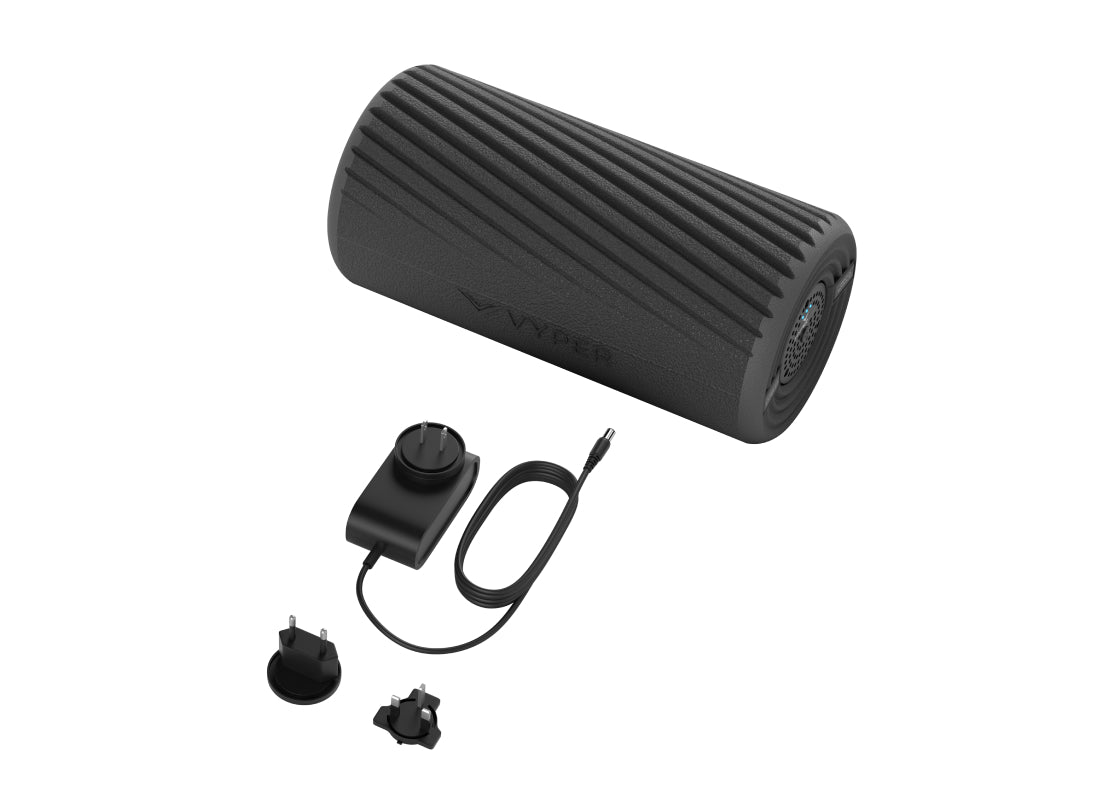 the cylinder shaped black Hyperice Vyper laying alonside the included charger and accessories