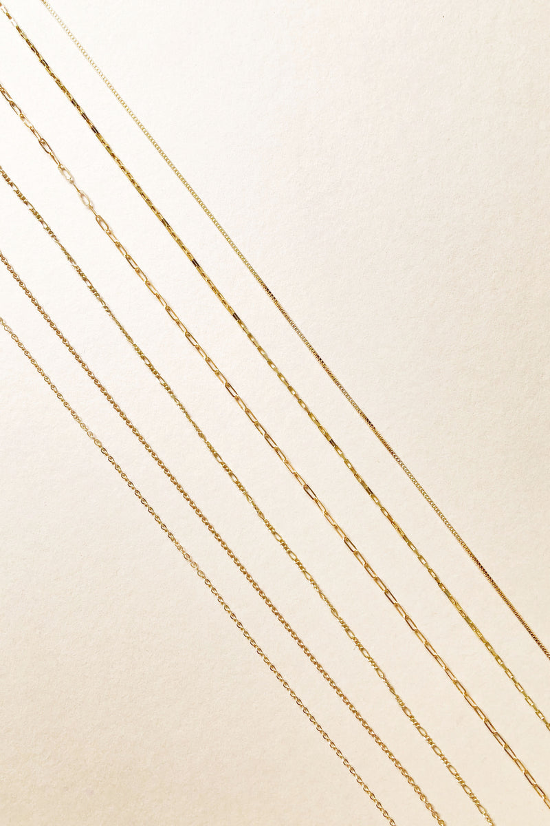 Petite Gold Chains.  Choose from Sparkle, Smooth Fine Cable, Baby Figaro, Drawn Cable, Baby Drawn Box and Box Chains.  All samples are lined up diagonally across the photo.