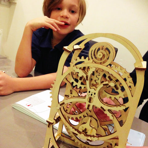 A child admires Ugears mechanical moidels