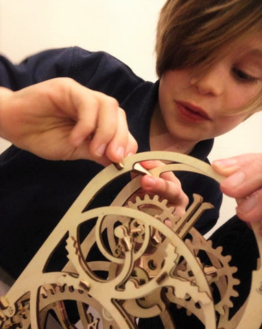 A boy putting together mechanical construction kit UGears