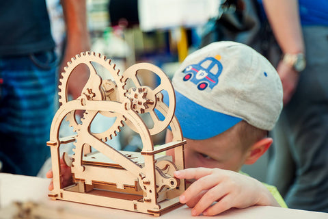 A child playing with UGears mechanical models