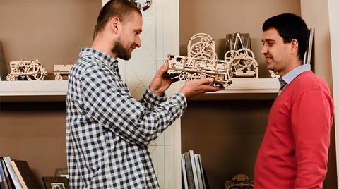 2 men admiring the assembled UGears Mechanical Models