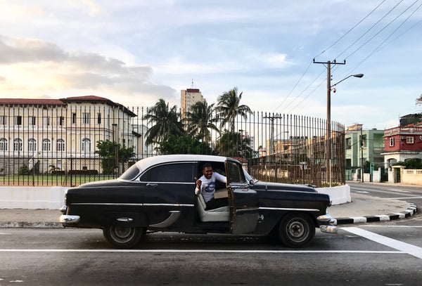 Hola! A Man saying hello from a classic 1950's car in Cuba