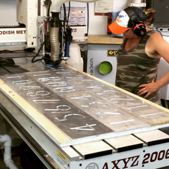 Susan Jones watches the process of machining aluminum house numbers in her Alberta shop.