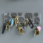 Magnetic Key Holder in brushed aluminum and black with circles.