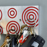 Magnetic Key Holder in brushed aluminum and red with circles.