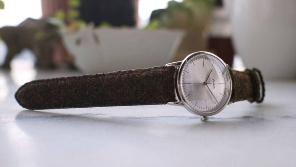 eclipse 38mm silver dress watch with harris tweed strap on table