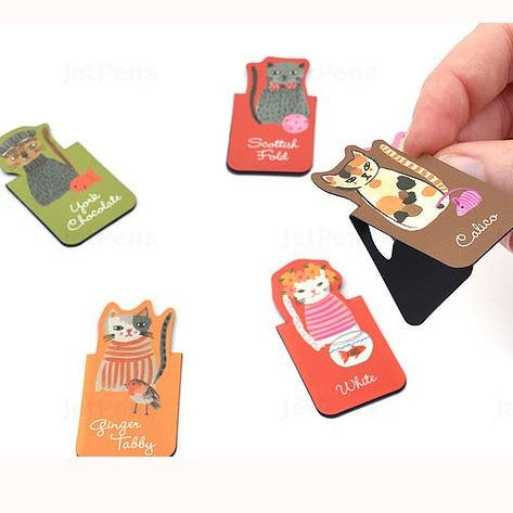 Cool Cats magnetic bookmarks unpackaged, fngers opening one to demo