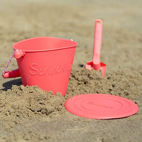 scrunch spade pink in background, bucket and frisbee in foreground on sand