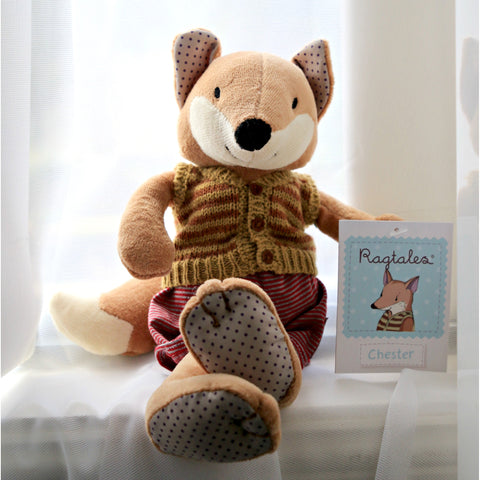Chester the fox sitting in window with ragtales label displayed
