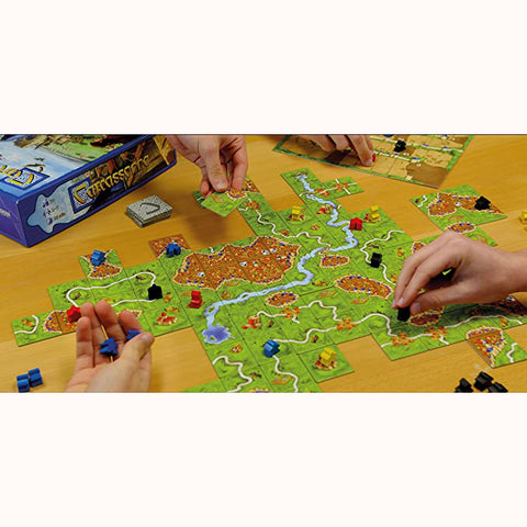 Carcassonne, hands playing game, meeples and tiles shown