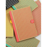 Orange Neon Kraft Notebook, with background of green & other notebooks