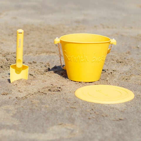 Scrunch Spade - Buttercup Yellow, on sand with bucket and frisbee