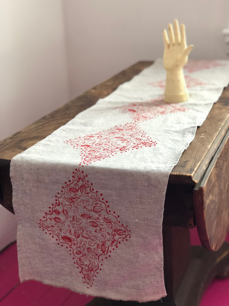 Linen table runner with red holy tangle design