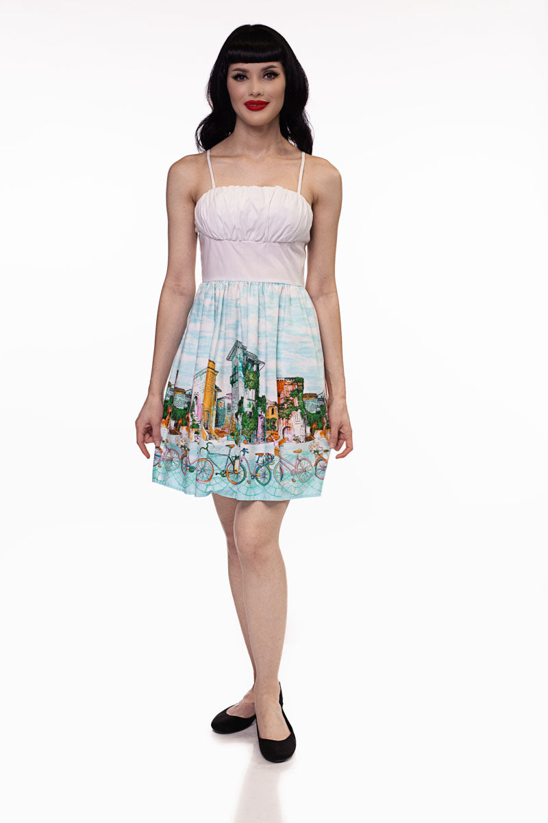 Model standing against white background wearing Alice in Wonderland print dress