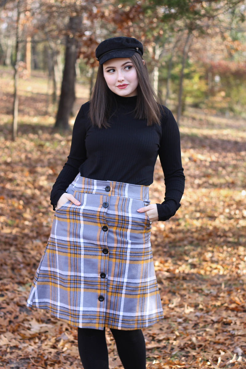 Model wearing grey plaid skirt with black beret in forest